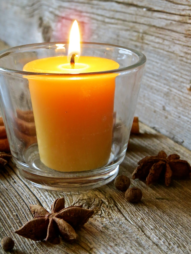A beeswax candle with spices and barnboard.