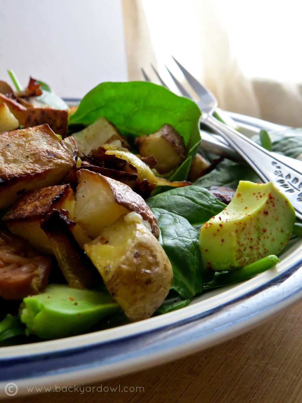 spinach salad with tempeh, avocado, and roast potatoes