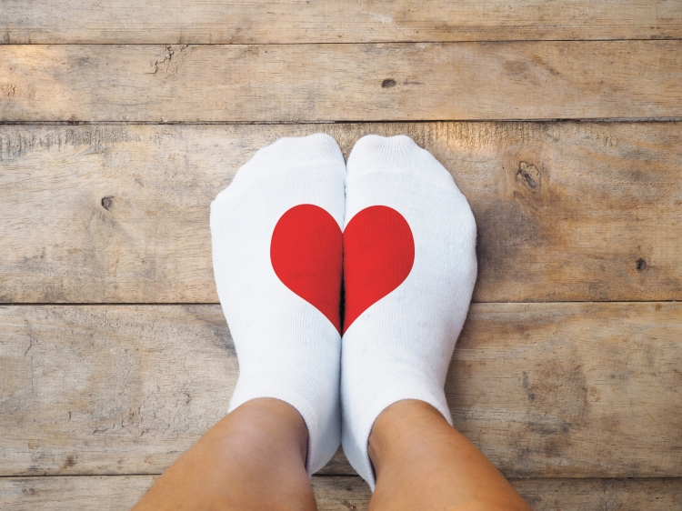Selfie feet wearing white socks with red heart shape on wooden floor background. Love concept. London, Ontario. Holistic Nutrition. About self love, cherishing yourself, stopping negative self-talk.