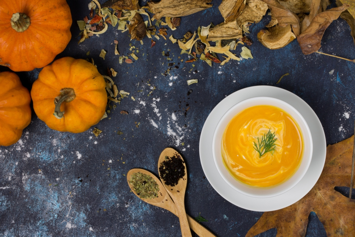Vegetable soup background with copy space. Dry leaves, miniature pumpkins, spices, dried vegetables around table. Close up directly above shot. Warming and comforting autumn soups with options for paleo, vegan, and gluten free